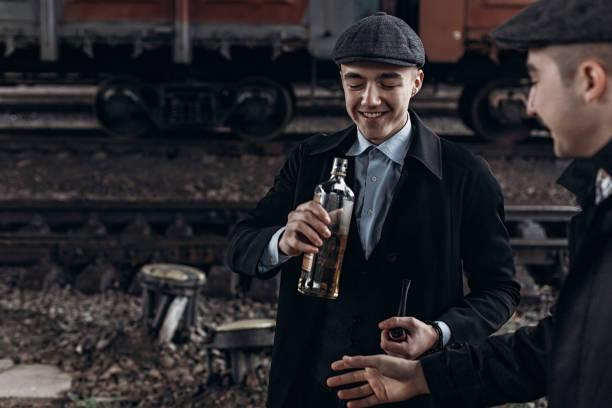 brutale gangster trinken auf dem hintergrund von eisenbahnwagen. england in den 1920er jahren thema. modische zuversichtlich mann. stimmungsvolle momente. platz für text. abgemagerter scheuklappen - scheuklappe stock-fotos und bilder