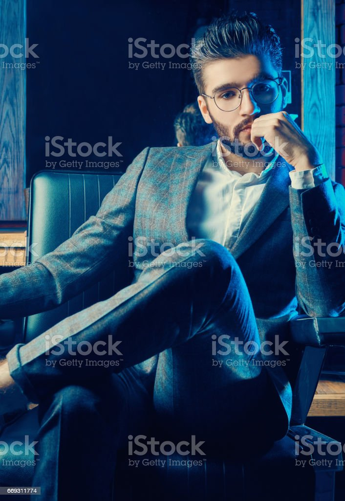 Brutal man in elegant suit and glasses in barbershop stock photo