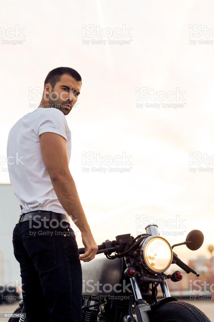 Homem brutal perto moto racer café personalizado. - foto de acervo