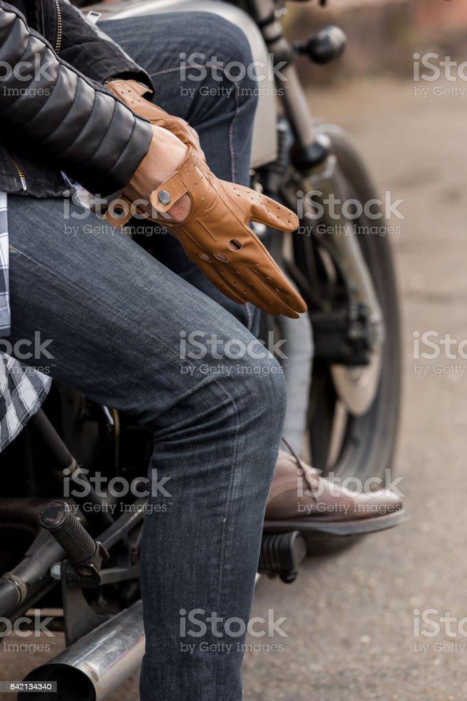 Brutal man sit on cafe racer custom motorbike. stock photo