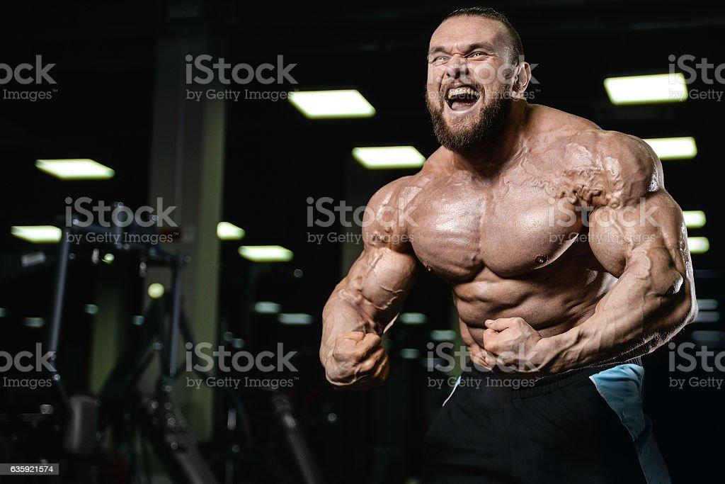 Brutal strong bodybuilder athletic men pumping up muscles with d - foto de acervo