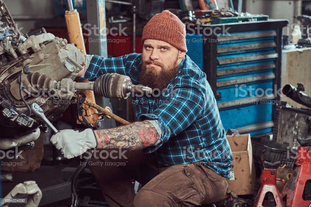 A brutal tattooed bearded mechanic specialist repairs the car engine which is raised on the hydraulic lift in the garage. Service station. stock photo