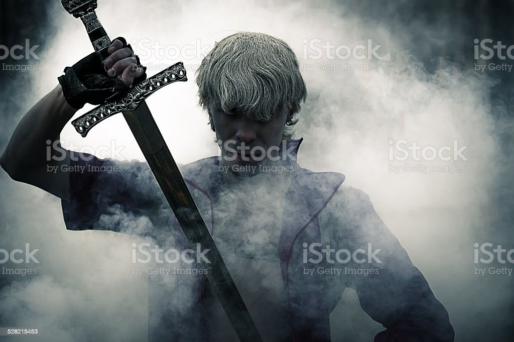 brutal warrior with sword in smoke stock photo