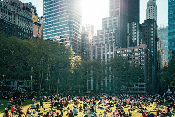 bryant park near the library in nyc crowded with people in the afternoon - public park stock photos and pictures