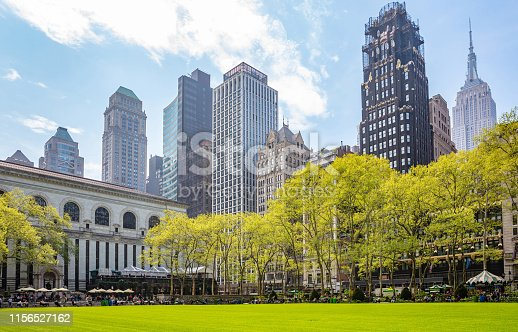 New York, Manhattan, Skyline view from Bryant park, springtime. Skyscrapers, people relaxing, green lawn and trees, clear blue sky background