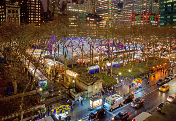 Bryant Park with Winter Village and Skating Rink at Night New York, USA - December 14, 2018:  Aerial View of Bryant Park at night showing the Winter Village, retail shops, Christmas Tree, Skating Rink, plane trees, people walking on 42nd Street, skating, with New York City Library building, The Bryant,, Bryant Park Hotel, Bank of China Building in the background, and cars lined up on 42nd street in the foreground bank of china stock pictures, royalty-free photos & images