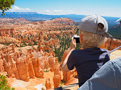 Bryce Canyon, Utah (USA) - 6 August 2016: A boy is taking a picture of the hoodoo rock formations at Bryce Canyon National Park, Utah (USA), while being held by his father.