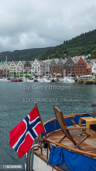 Bryggen, Bergen, Norway - July 30, 2018: famous colorful wood houses of the old historic harbor district in Bergen, part of the unique Hanseatic League heritage and a boat stern in the foreground.