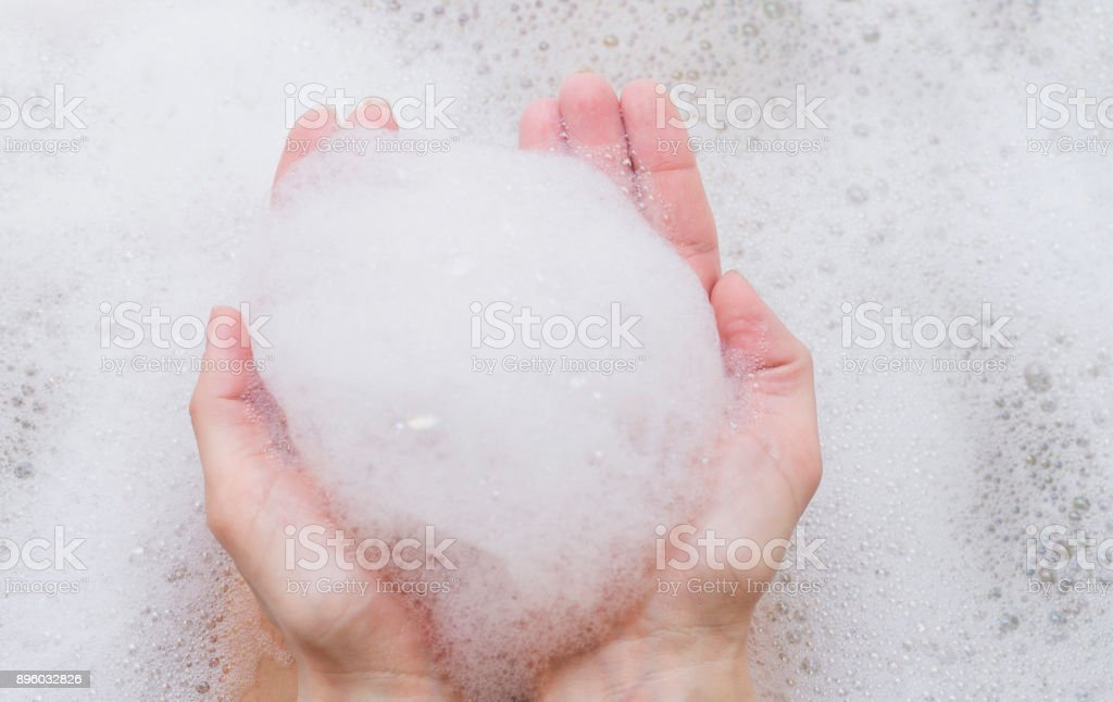 Bubble bath foam in woman's hands. Part of body, selective focus. stock photo