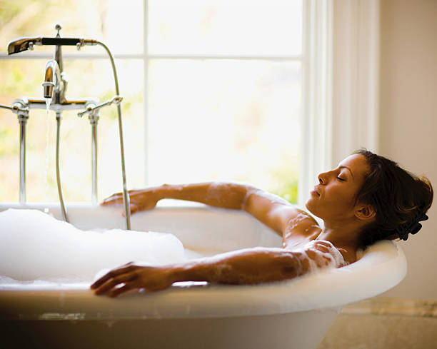 Bubble Bath A woman getting ready to take a bath. bathtub stock pictures, royalty-free photos & images