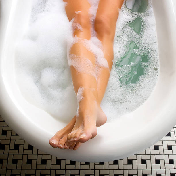 Bubble Bath A woman taking a bubble bath with the picture only showing her lower legs and feet out of the water. bubble bath stock pictures, royalty-free photos & images