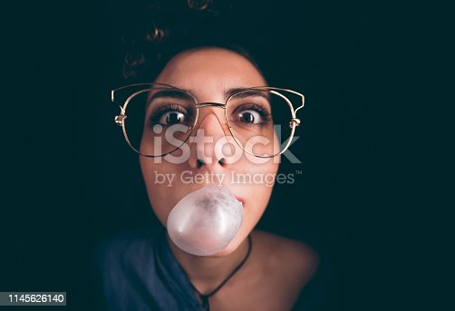 Young woman making bubble gum balloon in the dark, wearing eyeglasses.