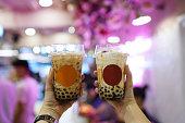 ミルクティー - 背景をぼかした写真に黒糖シロップ、黒真珠と新鮮な牛乳のプラスチック ガラス (ボバ) を持っている手をバブルします。