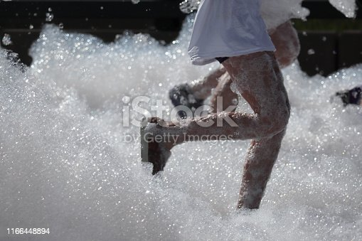 Denver, Colorado: Bubble Run in Lowry Sports Park. Running legs close up.