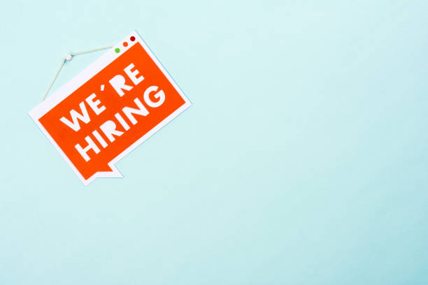 """Bubble speech hanging sign with phrase """"we are hiring"""" in the paper. Blue background, copy space or blank space. Bubble speech hanging sign with phrase """"we are hiring"""" in the paper. Blue background, copy space or blank space. help wanted sign stock pictures, royalty-free photos & images"""