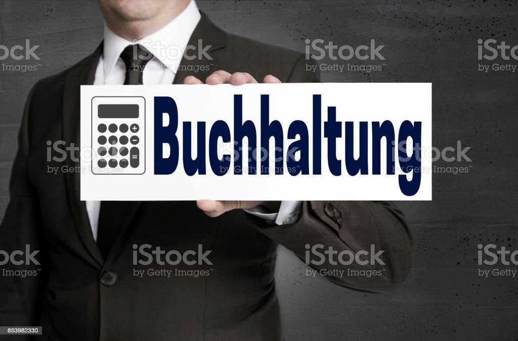 Buchhaltung (in german Accounting) signboard is held by businessman stock photo