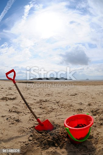 A childs plastic bucket and spade in the sand on a beach