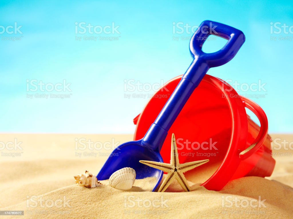 Bucket and Spade with Seashells on the Beach stock photo