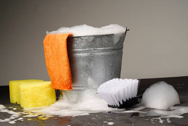 Bucket and Supplies for Car Wash Studio photograph of a bucket of soapy water with yellow sponge, brush and chamois.  bucket stock pictures, royalty-free photos & images
