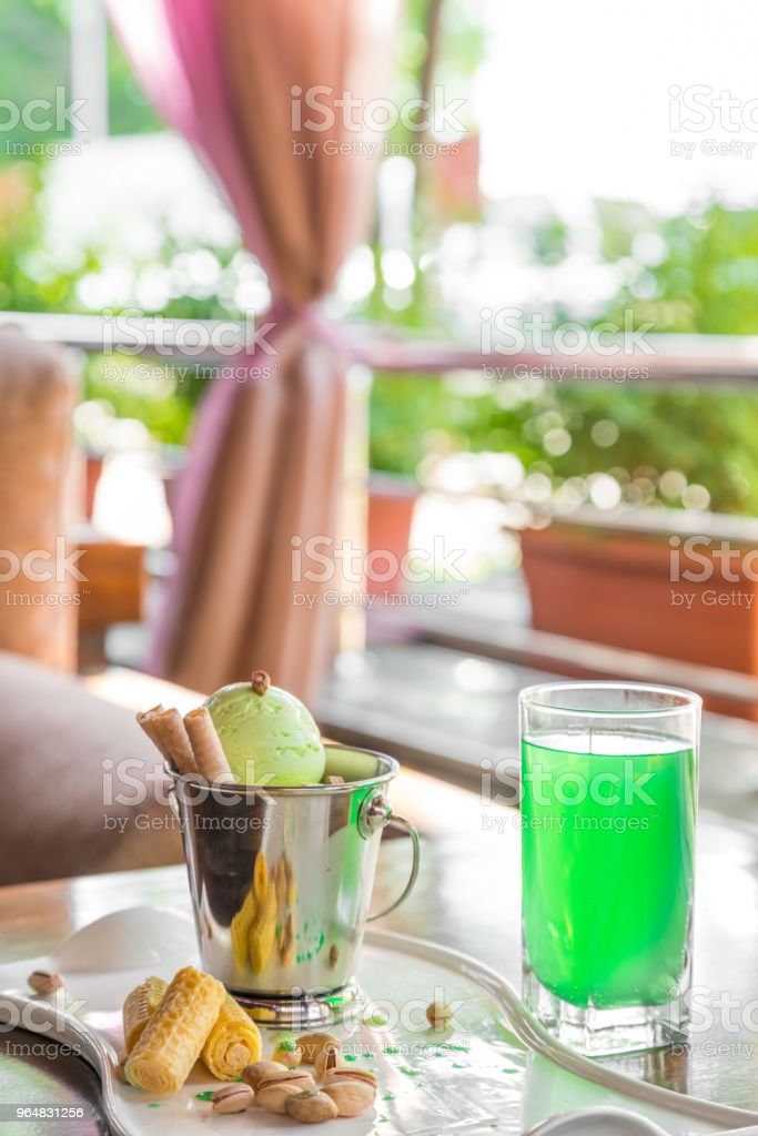 A bucket cup of pistachio ice cream topped with corn cones on white table in on the summer veranda royalty-free stock photo