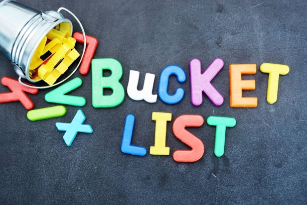 Bucket list concept, things to do in life with iron bucket and magnetic letters on chalkboard stock photo