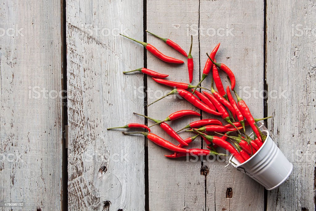 Bucket of Chilies A macro shot of a collection of red birds eye chilies, tumbling out of a small rustic bucket, on a worn wooden background, lit by natural daylight. 2015 Stock Photo