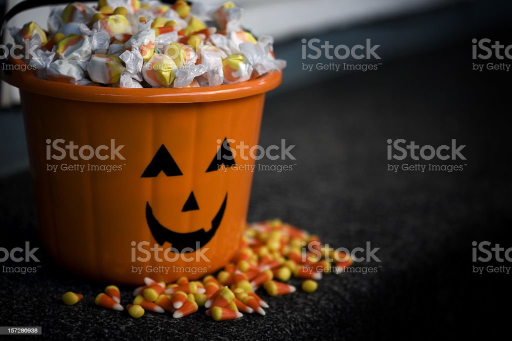 Bucket of Halloween Candy with Jack o Lantern, Copy Space stock photo