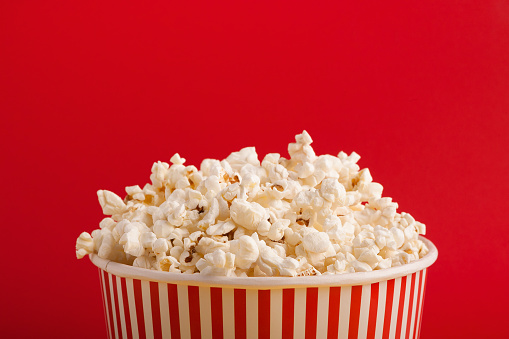 Bucket of popcorn on red background