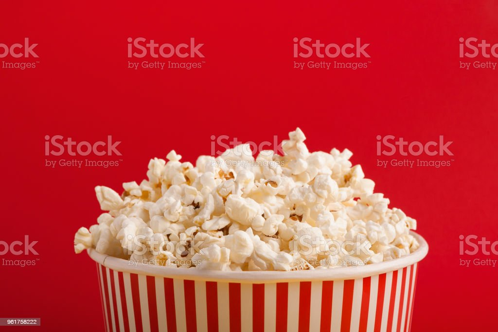 Bucket of popcorn on red background stock photo