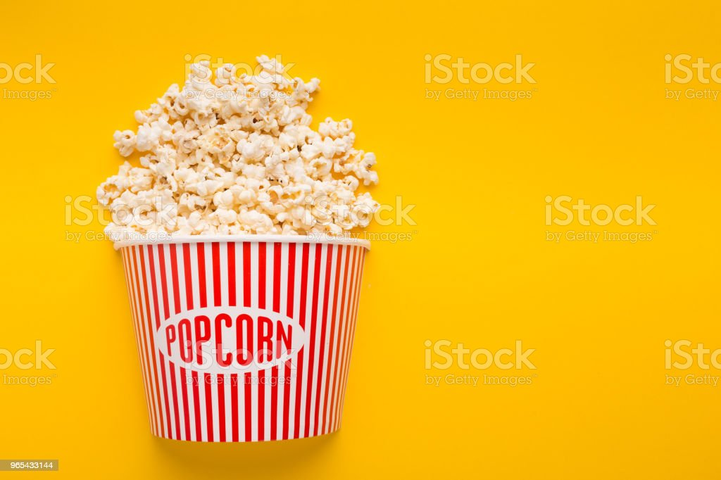 Bucket of popcorn on yellow background zbiór zdjęć royalty-free