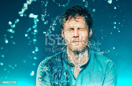 Man closes his eyes, as he is hit with a bucket of water. The water splashes from his face. The photo is shot at high speed sync.
