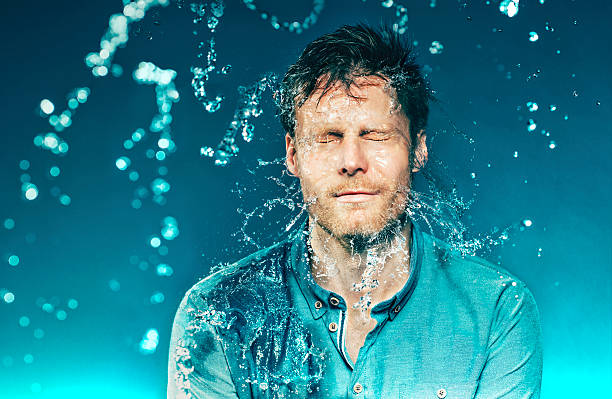 Bucket of water hits a man in the head Man closes his eyes, as he is hit with a bucket of water. The water splashes from his face. The photo is shot at high speed sync. slow motion stock pictures, royalty-free photos & images