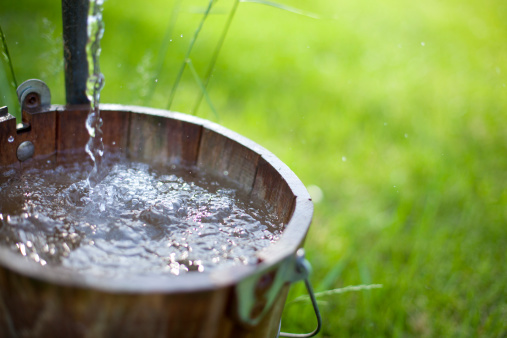 Fresh water from a well flows out into an old bucket. Shallow depth of field for focus on water.
