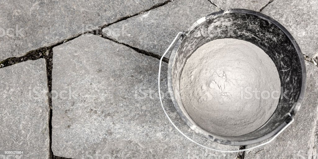 bucket with cement on a grey flagstone floor with unfilled joints stock photo