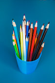 Bucket with colorful pencils on a blue background