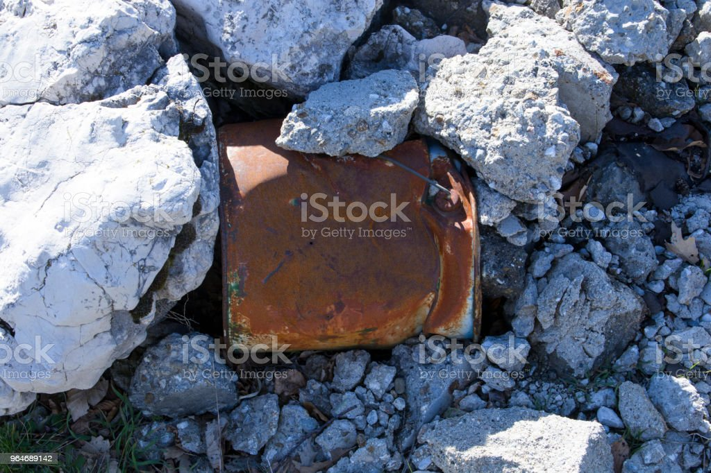 Bucket with rust between the rocks royalty-free stock photo