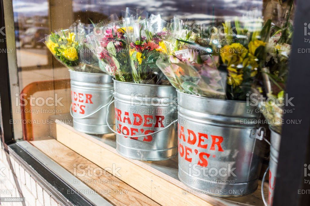 Buckets of flowers with Trader Joe's signs viewed from outside of store stock photo