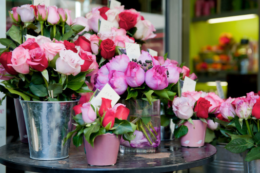 Buckets of fresh pink and red roses outside a florist shop