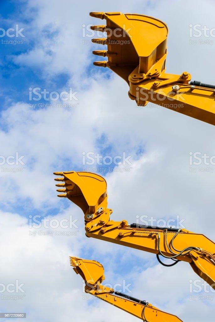 Eimer von drei Bagger Baggern vor blauem Himmel – Foto