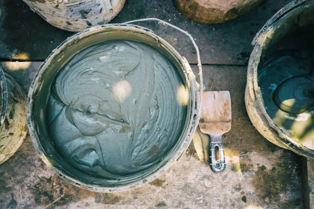eimer mit lösung des gebäudes kleber für wand verputzen, schaum-isolierung, fassade des hauses - betonkleber stock-fotos und bilder