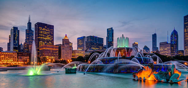 Buckingham Fountain and Skyline Buckingham fountain shot with a slow shutter speed to capture the colorful light changes and illuminated Chicago skyline in the background. chicago stock pictures, royalty-free photos & images