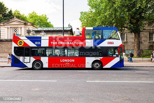 1125782554 istock photo Buckingham Palace and sign for Hop on Hop off The Original Tour double decker red white blue bus 1220843482