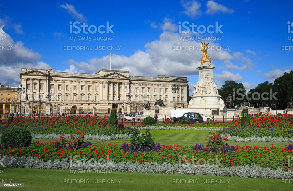 Buckingham Palace in London with flowerbeds and vibrant blue sky stock photo