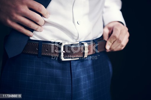 Cropped shot of a man wearing a belt with his jeans and shirt on his wedding day