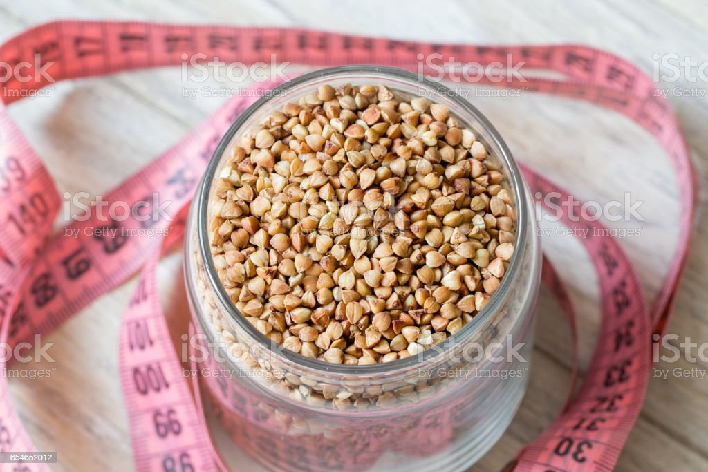 Buckwheat grain in glass bank and centimeter on a wooden background stock photo