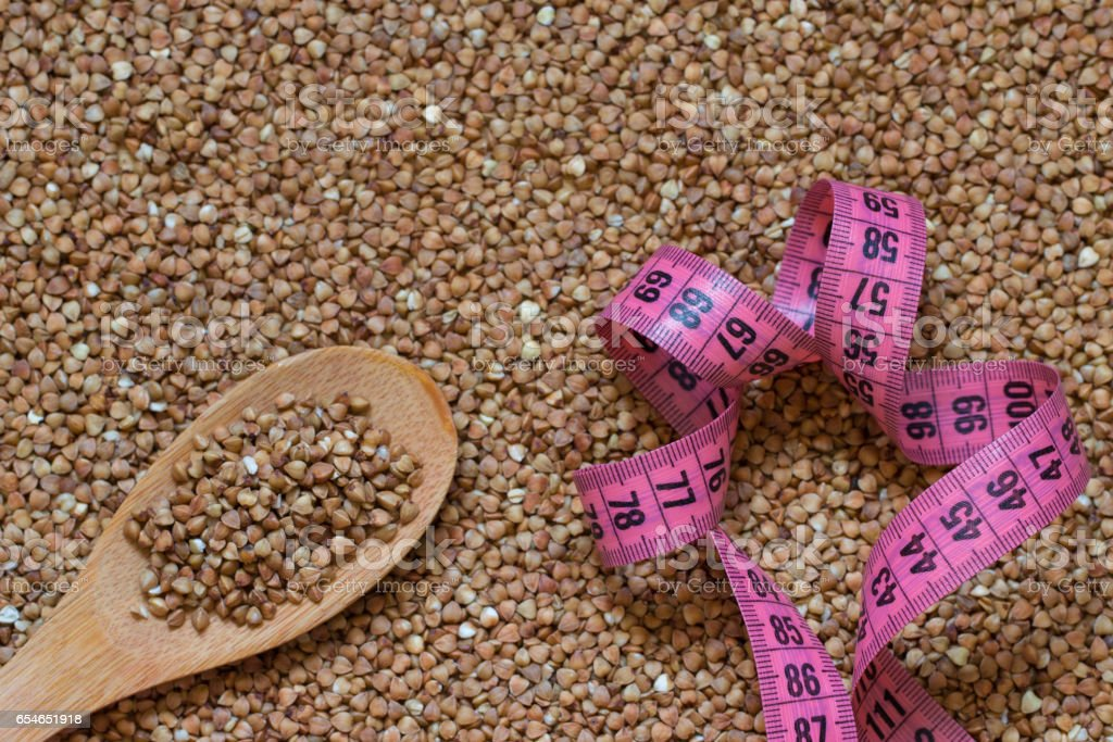 Buckwheat grain, wooden spoon and centimeter or food background stock photo