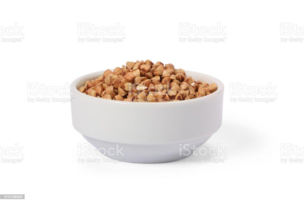 Buckwheat groats in whitebowl isolated on white background stock photo