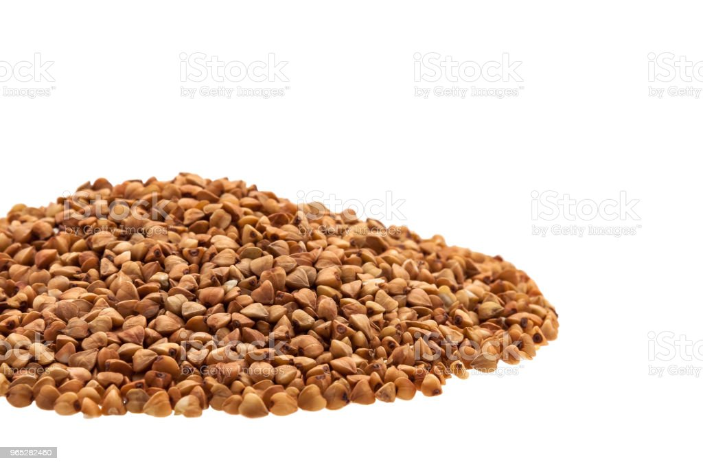 Buckwheat in a heap on the side on a white background. zbiór zdjęć royalty-free