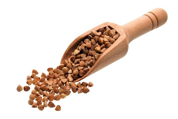 Buckwheat in a wooden scoop stock photo