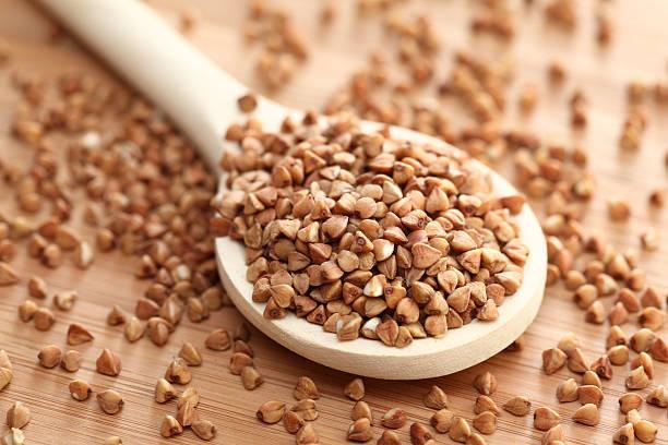 buckwheat in a wooden spoon - boekweit stockfoto's en -beelden
